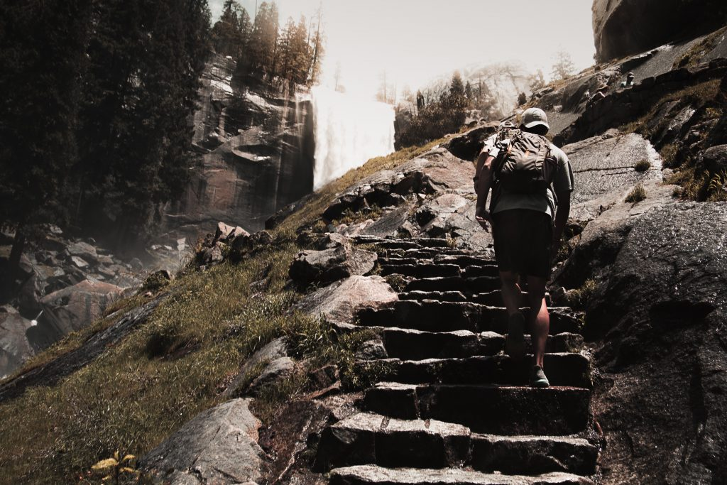 man walking up stone stairs near a waterfall at daytime